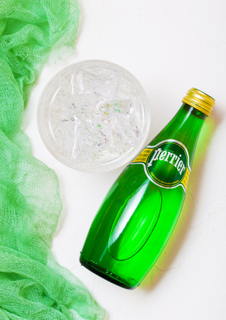 LONDON, UK - OCTOBER 10, 2018 : Bottle of Perrier sparkling water with glass and green cloth. Perrier is a French brand of natural bottled mineral water sold worldwide.