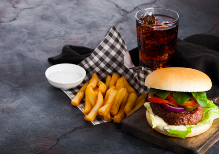 Fresh beef burger with sauce and vegetables and glass of cola soft drink with potato chips fries on stone kitchen background. 免版税图像