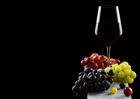 Elegant glass of red wine with dark and red and green grapes on wooden board on black background.