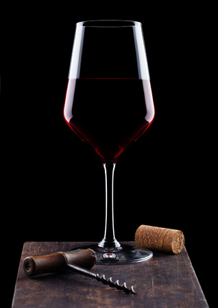 Glass of red wine with vintage corkscrew opener and cork on wooden board on black