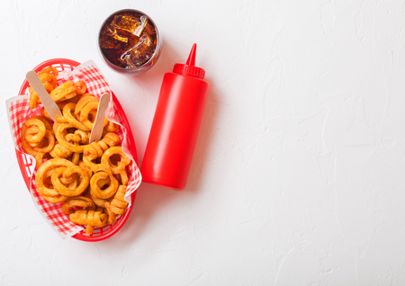 Curly fries fast food snack in red plastic tray with glass of cola and ketchup on kitchen background. Unhealthy junk food Фото со стока