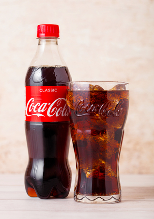 LONDON, UK - AUGUST 03, 2018: Plastic bottle and original glass of Original Coca Cola soft drink on wood. Most popular drink in the world.