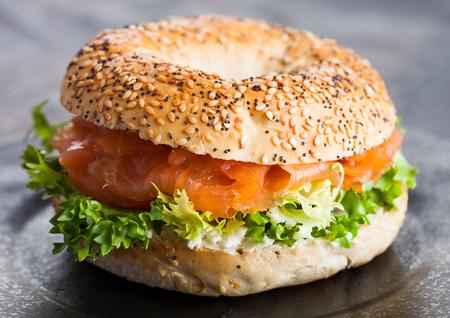 Panino sano fresco del bagel con il salmone, la ricotta e la lattuga in banda nera sul fondo scuro del tavolo da cucina.