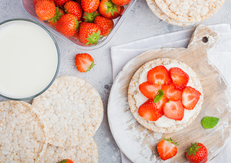 Healthy organic rice cakes with ricotta and fresh strawberries and glass of milk on light stone kitchen background.