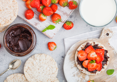 Healthy organic rice cakes with chocolate butter and fresh strawberries on wooden board and glass of milk on light stone kitchen background.