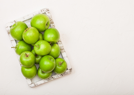 Green healthy organic apples in vintage box on wood background