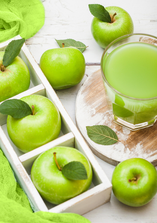 Glass of fresh organic apple juice with green apples in box on wood background.