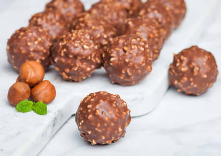 Luxury chocolate candies with hazelnuts pieces and mint leaf on marble background.