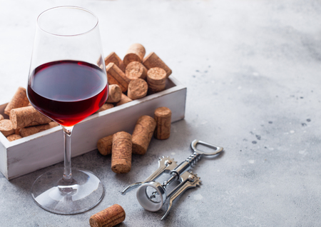 Elegant glass of red wine with box of corks and opener on kitchen table background.