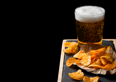 Glass of lager beer with potato crisps snack on stone board on black background.