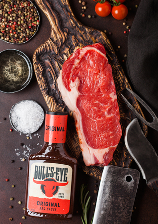 LONDON, UK - DECEMBER 13, 2018: Bottle of Bulls Eye Original Barbeque sauce with raw sirloin beef steak on vintage chipping board with knife and fork on rusty board
