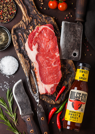 LONDON, UK - DECEMBER 13, 2018: Bottle of Bulls Eye Sweet and Spicy sauce with raw sirloin beef steak on vintage chipping board with knife and fork on rusty board Editorial