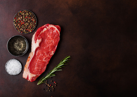Raw sirloin beef steak on rusty background. Salt and pepper with fresh rosemary and bowl of oil.