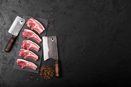 Fresh raw butchers lamb beef cutlets on stone board with vintage hatchets on black background. Archivio Fotografico