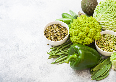 Assorted green toned raw organic vegetables on white background. Avocado, cabbage, broccoli, cauliflower and cucumber with trimmed mung beans in white bowl and loose pepper. Space for text