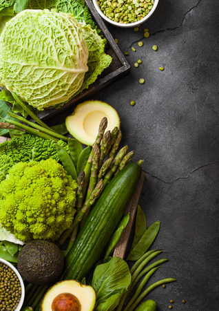 Assorted green toned raw organic vegetables on dark background. Avocado, cabbage, broccoli, cauliflower and cucumber with trimmed beans.