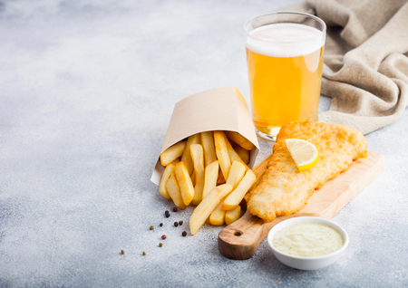 Traditional British Fish and Chips with tartar sauce abd glass of craft lager beer on chopping board on white stone table background. Stok Fotoğraf