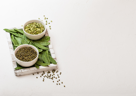 Bowl of  mung beans and split peaswith raw organic mangetout in vintage wooden box on white kitchen backround Imagens