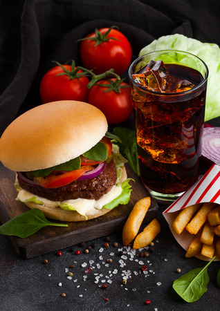 Fresh beef burger with sauce and vegetables and glass of cola soft drink with potato chips fries on stone kitchen background. Banco de Imagens