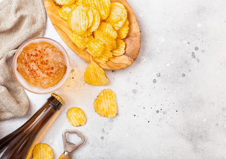 Glass and bottle of craft lager beer with potato crisps snack and opener on stone kitchen table background. Beer and snack.