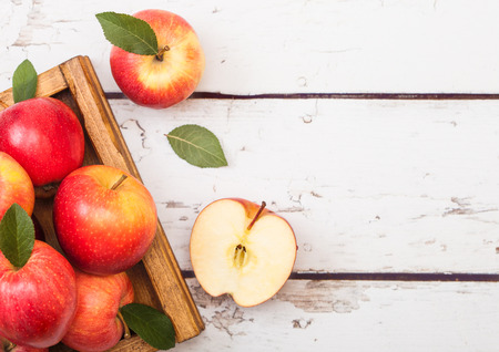 Red organic healthy apples in vintage box on wooden background. Imagens