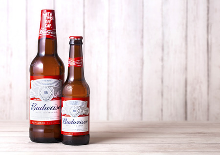 LONDON, UK - FEBRUARY 06, 2019: Glass bottles of Budweiser Beer on wooden background. An American lager first introduced in 1876.