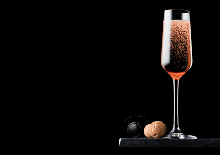 Elegant glass of pink rose champagne with cork and wire cage on black marble board on black background. Stock Photo