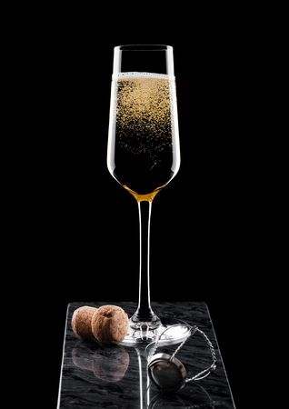 Elegant glass of yellow champagne with cork and wire cage on black marble board on black.