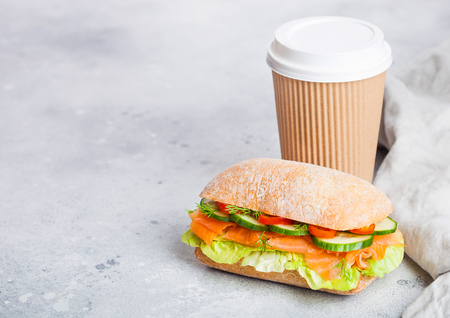 Fresh healthy salmon sandwich with lettuce and cucumber with paper cup of coffee on white stone background. Breakfast snack.