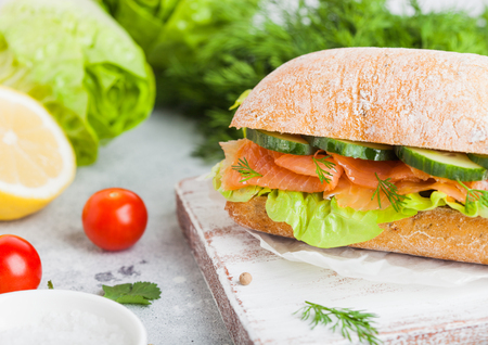 Fresh healthy salmon sandwich with lettuce and cucumber on vintage chopping board on stone background. Breakfast snack. Fresh tomatoes, dill and lemon.
