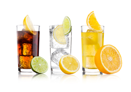Glasses of cola and orange soda drink and lemonade sparkling water on white background with ice cubes lemons and lime bits Archivio Fotografico