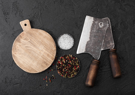 Vintage meat knife hatchets with vintage chopping board and black table background. Butcher utensils. Close up.
