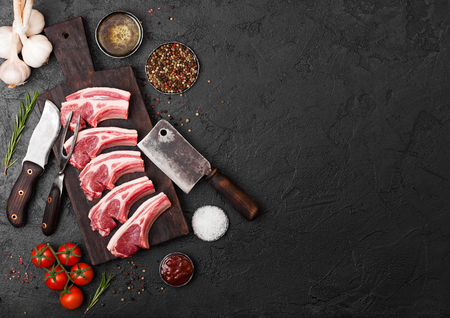 Fresh raw butchers lamb beef cutlets on stone board with vintage meat fork and knife and hatchet on black background.Salt, pepper and oil with tomatoes and garlic and barbecue sauce. Stock fotó