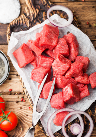 Raw lean diced casserole beef pork steak on chopping board with vintage fork on wooden background. Salt and pepper