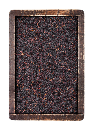 Wooden box of raw organic black venus rice on white background.Top view Imagens - 118963440