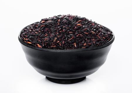Black bowl of raw organic black venus rice on white background.