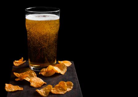 Glass of lager beer with potato crisps snack on vintage wooden board on black background. Reklamní fotografie