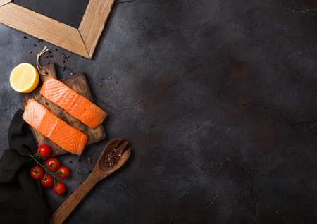 Plastic container with fresh salmon slice with oil tomatoes and lemon on stone kitchen background Reklamní fotografie