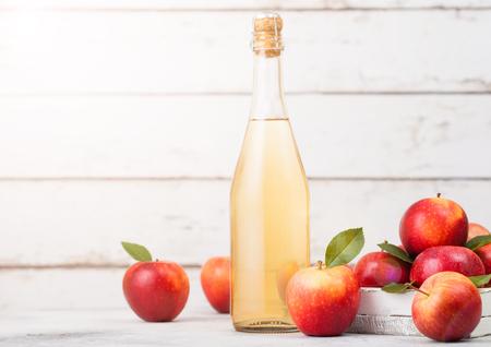 Botella de sidra de manzana orgánica casera con manzanas frescas en caja sobre fondo de madera, vaso con cubitos de hielo