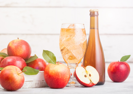 Bottle and glass of homemade organic apple cider with fresh apples in box on wooden background, Glass with ice cubes