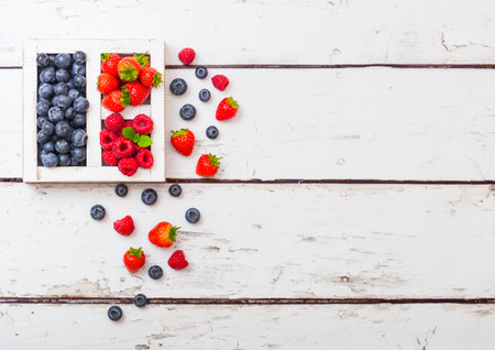 Fresh raw organic berries in white wooden box on wood background. Space for text. Strawberry, Raspberry, Blueberry and Mint leaf