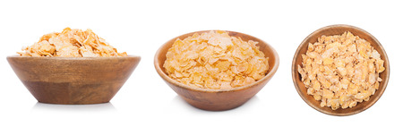 Bamboo wood bowl with natural organic granola cereal corn flakes on white.Top view