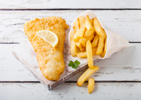 Traditional British Fish and Chips with tartar sauce on chopping board on white wood background.