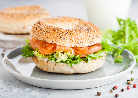 Fresh healthy bagel sandwich with salmon, ricotta and lettuce in grey plate on light kitchen table background. Healthy diet food.