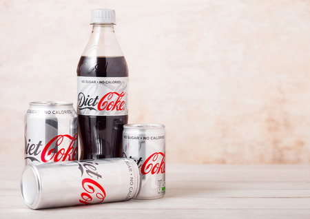 LONDON, UK - AUGUST 03, 2018: Plastic bottle and aluminium tins of Diet Coke Coca Cola soft drink on wood. Most popular drink in the world.