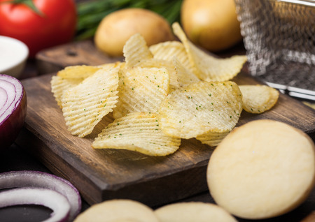 Fresh organic homemade potato crisps chips with sour cream and red onions on chopping board on dark wooden background. Stock Photo