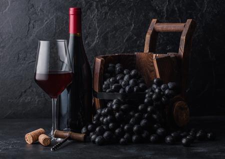 Elegant glass and bottle of red wine with dark grapes inside vintage wooden barrel on black stone background. Corks and corkscrew on board