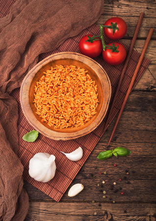 Wooden plate bowl of rice with tomato and basil and garlic and chopsticks on brown bamboo place mat on wood background with dark cloth. Top view.