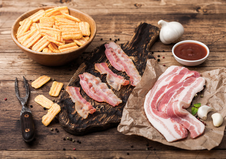 Bacon flavored snacks chips with grilled bacon rashers on vintage chopping board with smoked raw bacon on butchers paper with garlic and sauce on wood background.