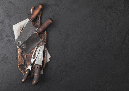 Vintage meat knife and fork and hatchets with vintage chopping board and black table background. Butcher utensils.